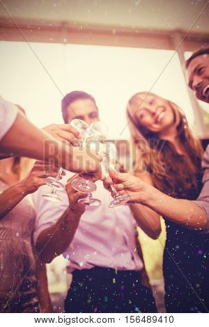 Cropped image of hand toasting champagne flute against flying colours
