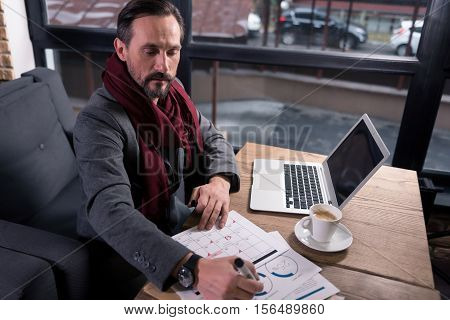 Making the report. Handsome hard working self employed man sitting at the table and looking at the calendar while creating a work schedule
