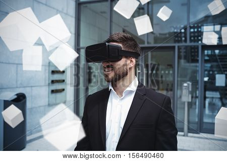 Digitally generated grey cubes floating against businessman using virtual reality headset