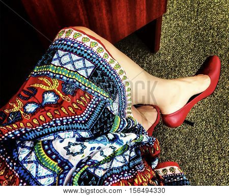 Business woman sitting at desk looking down on colorful office clothing non traditional business casual dress code with red high heel shoes symbolizing creativity and leadership in the workplace