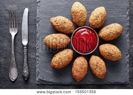 Kibbeh traditional beef, lamb, goat or camel meat stuffed bulgur kofta spicy meatball fried croquettes dinner food on dark table background