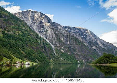 Neroy fjord steep mountain slopes and small village under the hill with ferry moored. Norway landscapes.