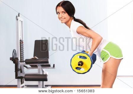 Foto des aktiven Mädchen stehen auf dem Boden und heben der Hantel in der Sportclub