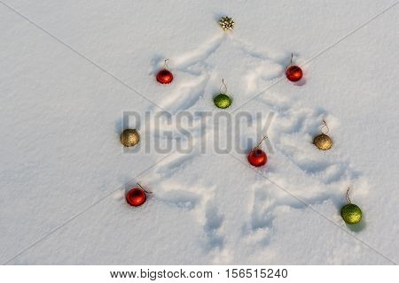 Christmas tree drawn in the snow and adorned with red golden and green ornaments
