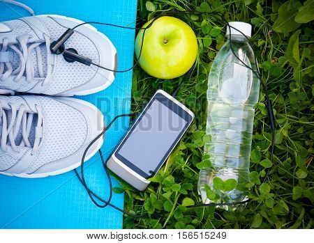Sports shoes sneakers on yoga mat and smartphone with headphones and apple on fresh green grass. Sports in the open air. top view