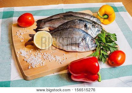 Fresh fish and vegetables on wooden cutting board
