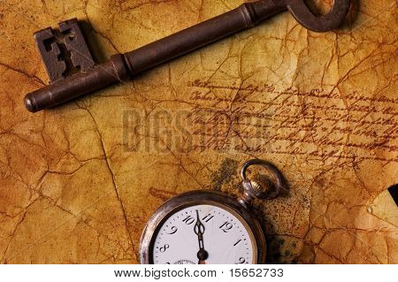 The old key with a clock on the textured paper