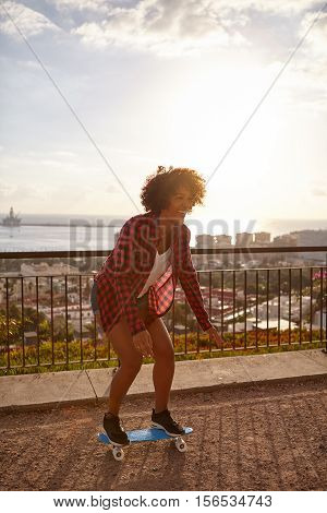 Skateboarding girl on a paved bridge overlooking a city with a bay further behind wearing casual clothing