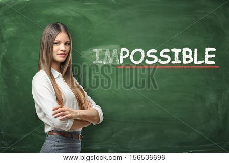 A young woman who made the word 'possible' from the word 'impossible' written on the green chalkboard wall. Make every effort. Optimistic and positive vision of the future. There is nothing we can't do if we work hard.