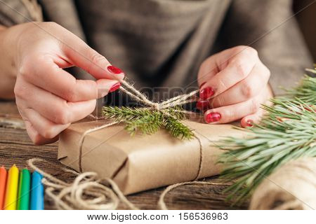 Woman's Hands Wrapping Christmas Holiday Handmade Present In Craft Paper With Twine Ribbon. Making B