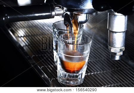 Espresso machine brewing a coffee in bar. Coffee pouring into shot glasses. Italian traditional morning short drink on breakfast. Close-up.