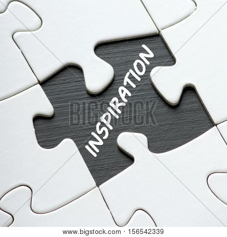 A missing jigsaw puzzle piece reveals the word Inspiration as a concept for unlocking ideas and solutions