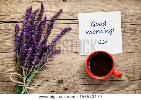 Flowers of salvia coffee cup and paper with Good morning text on wooden table top view