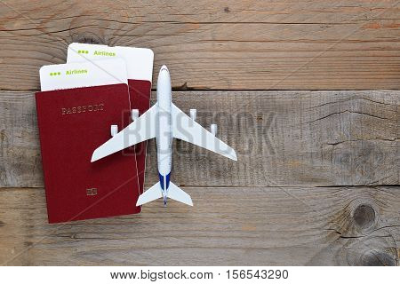 Passports boarding passes and toy airplane on wooden table
