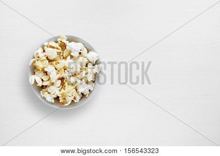 Popcorn in bowl on white table top view