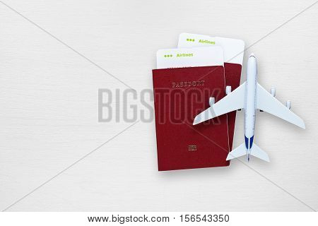 Passports boarding passes and toy airplane on white table
