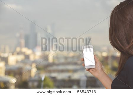 Woman with dark hair holding blank white cellular phone on blurry city background. Mock up