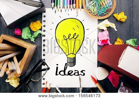 Top view of messy office desktop with colorful supplies and creative lamp sketch. Idea concept