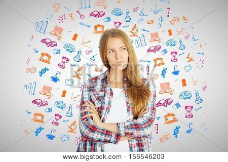 Thoughtful caucasian girl with colorful icons. Education concept