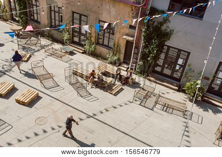 TBILISI, GEORGIA - OCT 9, 2016: People having fun in grunge area of city with artistic galleries and weird benches around on October 9, 2016. Tbilisi has a population of 1.5 million people
