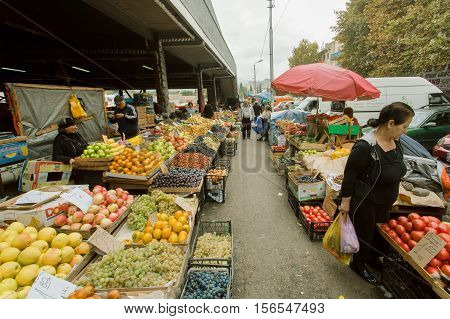 TBILISI, GEORGIA - OCT 12, 2016: Buyers and traders of city market with stands of fresh fruits and vegetables on October 12, 2016. Tbilisi has a population of 1.5 million people