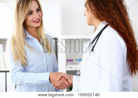 Female Doctor Shake Hand As Hello With Beautiful Blonde Patient
