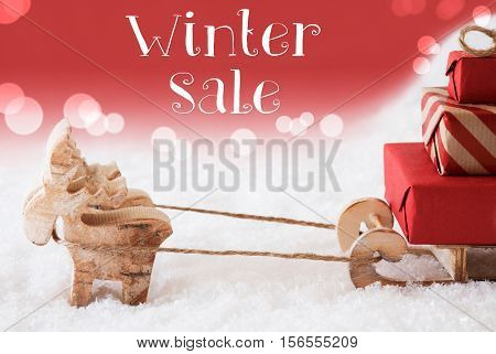 Moose Is Drawing A Sled With Red Gifts Or Presents In Snow. Christmas Card For Seasons Greetings. Red Christmassy Background With Bokeh Effect. English Text Winter Sale