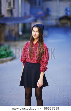 Sweet modest girl in red plaid blouse and black short skirt standing on one of St. Petersburg streets.