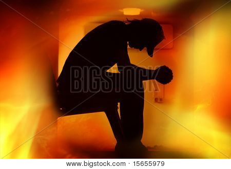Silhouette of teen praying with flames around