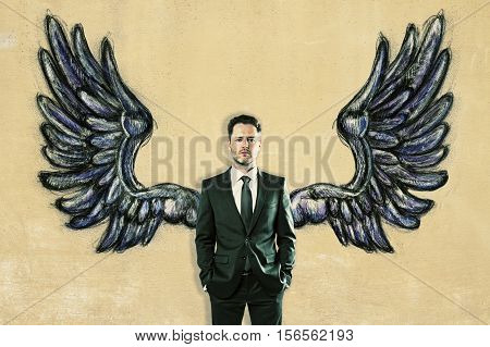 Businessman with drawn wings on textured background. Freedom concept