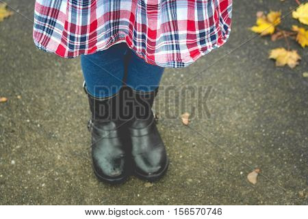 Little girl with leggings and boots and patriotic skirt in the fall.