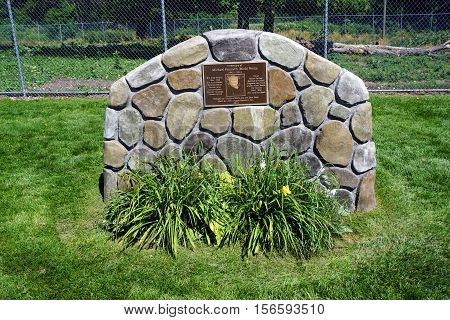 HARBOR SPRINGS, MICHIGAN / UNITED STATES - A bronze plaque, in memory of Michael Kenneth (Mick) Heinz, is attached to a stone wall in the Harbor Springs Deer Park.