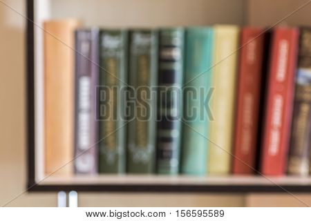 Books on a shelf out of focus as a background.