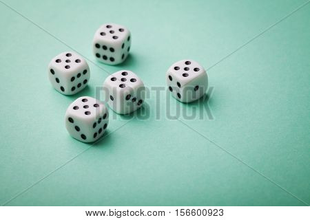 White dice on green background. Gambling devices. Copy space for text. All number five. Game of chance concept.