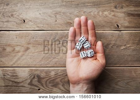 Man holding in hand white dice over the wooden table from above. Gambling devices. Game of chance concept.