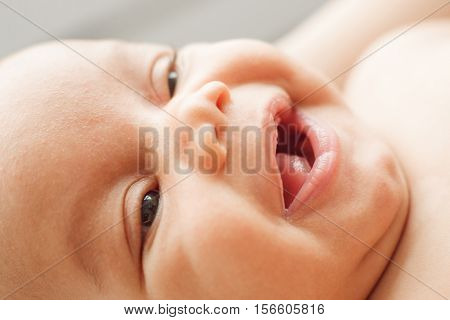 Face of laughing newborn child. Portrait of happy glad baby, widely smiling at his mom. Childhood, innocence, infant, happiness, family concept