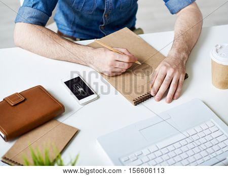 Businessman drawing graphs in his sketch pad, smart phone with low battery charge symbol lying on table