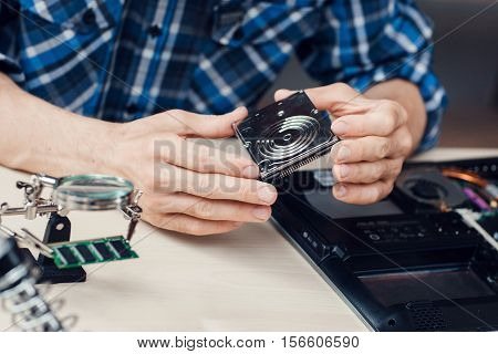 Engineer holding winchester disk in hands. Close-up photo of important computer component in hands. Electronic repair shop. technology development and construction concept