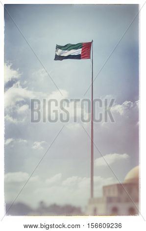 Flag of United Arab Emirates flying high. An image with old grunge look. An old archival vintage effect.