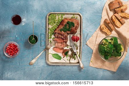Sliced medium rare grilled steak on the vintage iron tray on blue stone surface top view