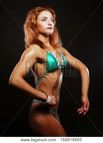 blond bodybuilder woman in bikin on black background