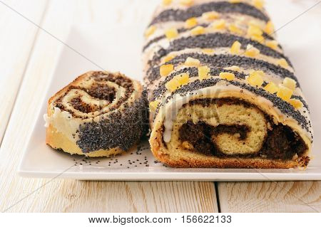 Poppy seed roll on white wooden background.