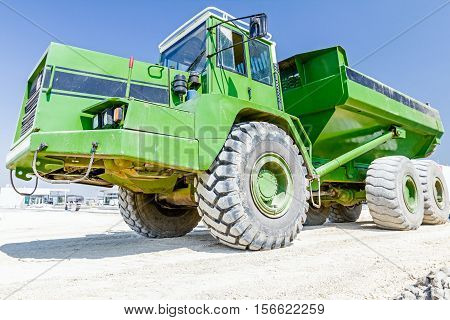 View on front end of big hydraulic dumper truck going over sandy ground at building site.