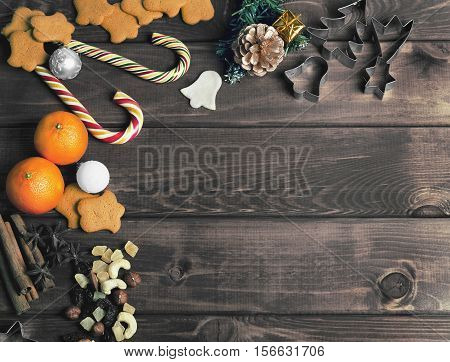 On wooden background Christmas composition - candy cane dough figurines Christmas-tree branch Christmas balls sweet raisins nuts cinnamon sticks cookies star anise sweet mandarins. Christmas sweets. Top view blank space