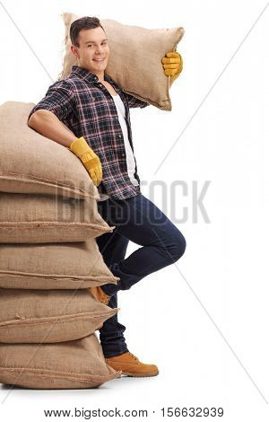 Agricultural worker with a burlap sack on his shoulder leaning on a stack of burlap sacks isolated on white background