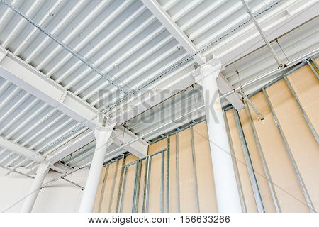 Low angle view on structure girders with metal skeleton at indoor ceiling construction.
