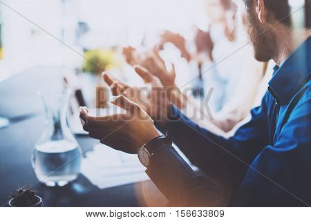 Close up view of young business partners applauding to reporter after listening speech at seminar. Professional education, work meeting, presentation or coaching concept.Horizontal, blurred background