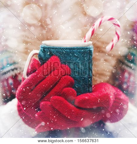 Woman holds a winter cup close up. Woman hands in woolen red gloves holding a cozy mug with hot coco