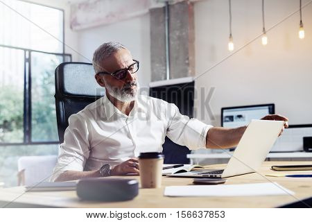 Middle age top manager wearing a classic glasses and working at the wood table in modern interior design office.Stylish bearded businessman using laptop on workplace. Horizontal, blurred