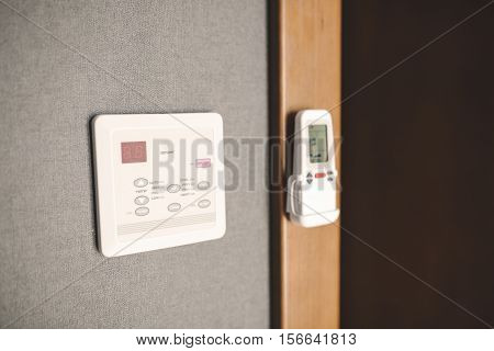 Programmable thermostat in room for adjusting temperature